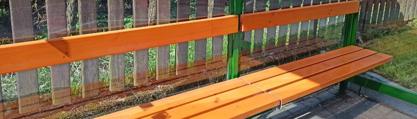 Zdjęcie przedstawia ławkę na przystanku autobusowym
